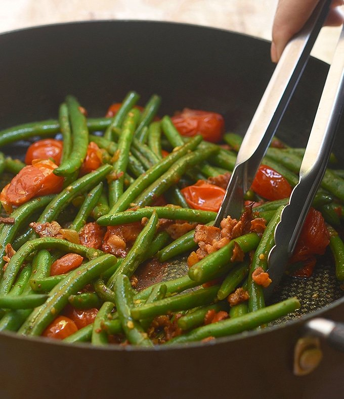 serving Green Beans with Bacon and Tomatoes with tongs