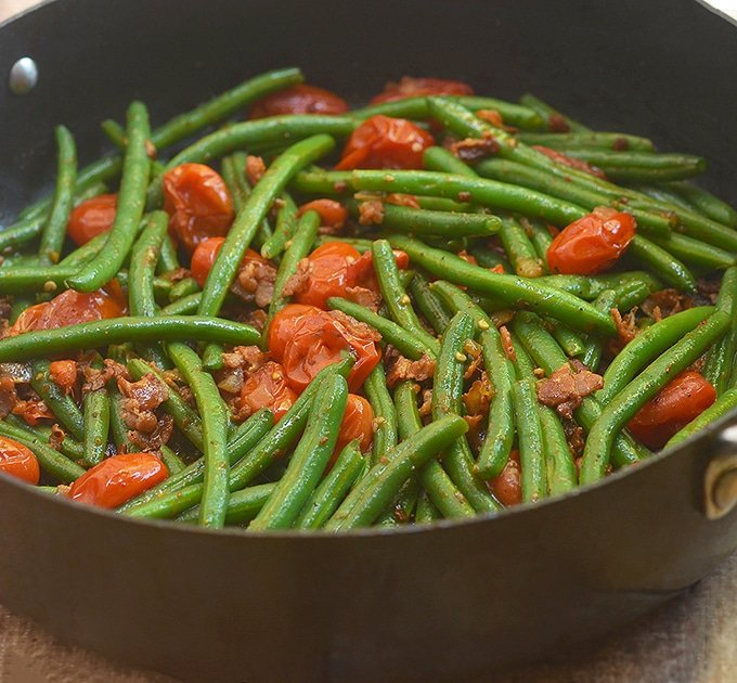 green beans and bacon with tomatoes in a skillet