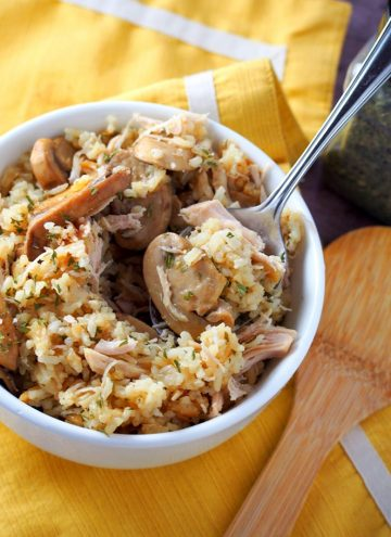 serving Instant pot rice casserole with chicken and mushrooms from a white bowl