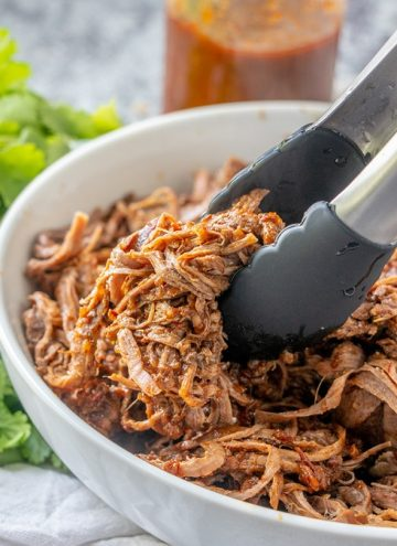 serving Slow Cooker Beef Barbacoa from a white bowl with tongs