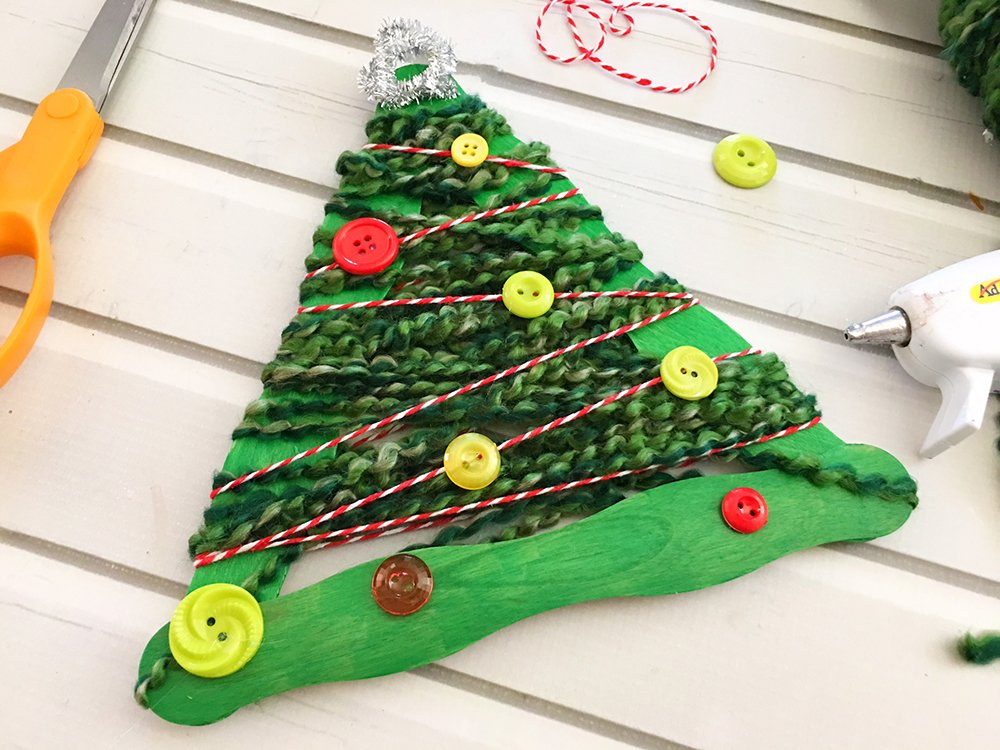 Yarn-Wrapped Christmas Tree Craft Stick Ornaments are a great holiday project for the whole family. They're so easy to make and a festive addition to your Christmas decor-glue buttons to decorate craft stick tree
