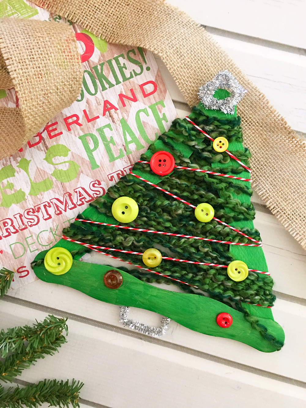 Yarn-wrapped Christmas tree craft stick ornaments are a great holiday project for the whole family. They're so easy to make and a festive addition to your Christmas decor-glue silver pipe cleaner on bottom of craft stick tree to resemble a tree trunk.