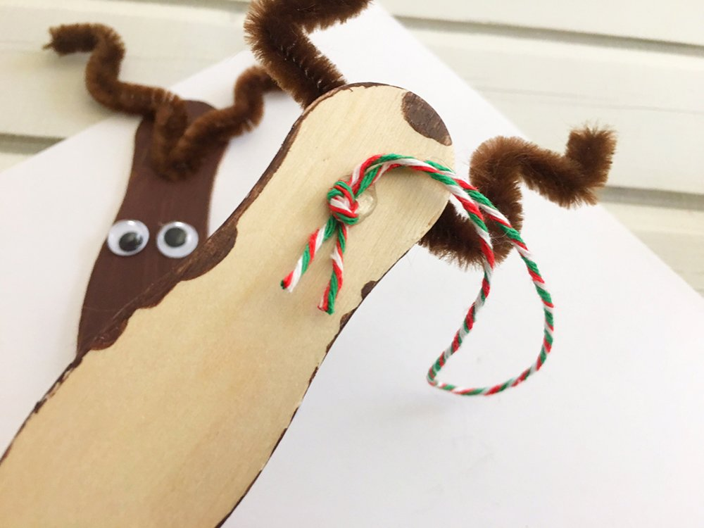tie a twine into a loop and glue at the back of the craft sticks to hang the reindeer ornament