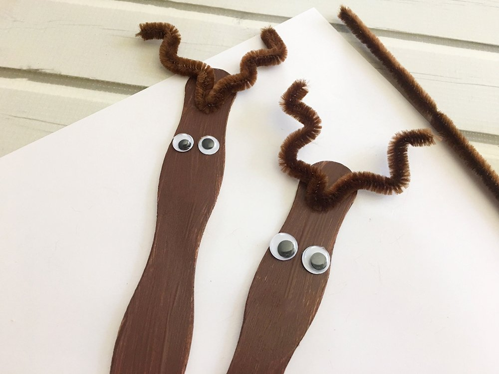 Craft Stick Reindeer Ornaments are an easy and fun Christmas craft to do with the whole family. Super adorable as tree decorations or gift package toppers-glue antlers onto craft stick and glue googly eyes below the antlers