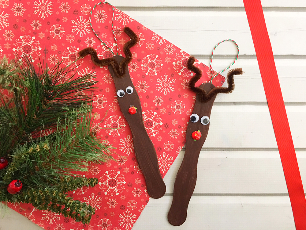 Craft Stick Reindeer Ornaments are an easy and fun Christmas craft to do with the whole family. Super adorable as tree decorations or gift package toppers-sprinkle glitter on the red nose