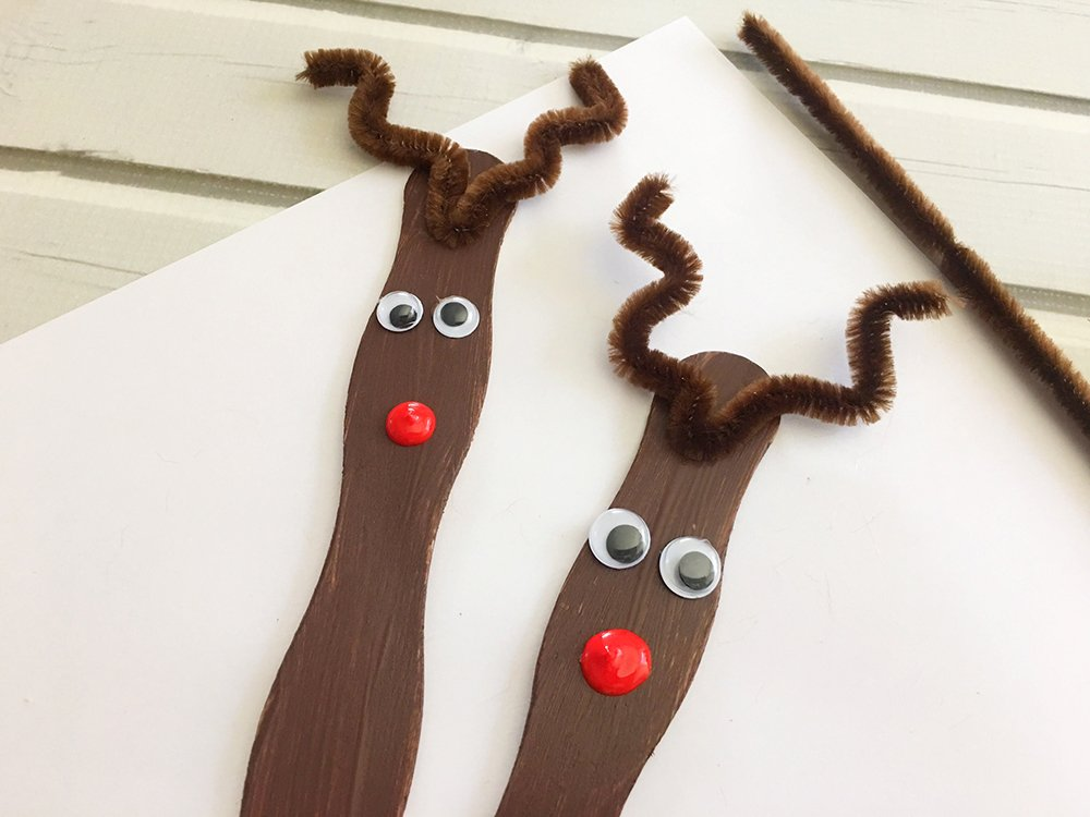 Craft Stick Reindeer Ornaments are an easy and fun Christmas craft to do with the whole family. Super adorable as tree decorations or gift package toppers-put a nose on craft stick using red puffy paint