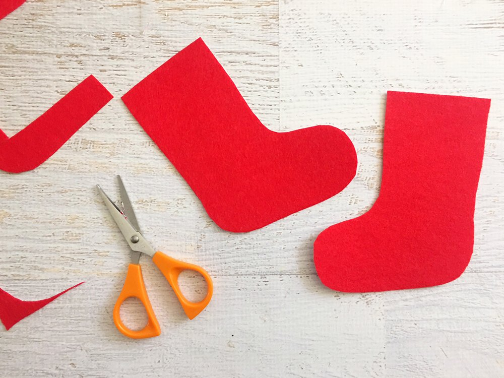 Felt Stocking Christmas Ornaments are an adorable addition to any holiday decor. So easy and fun to make with simple crafts supplies-draw and cut out sock shapes on red felt