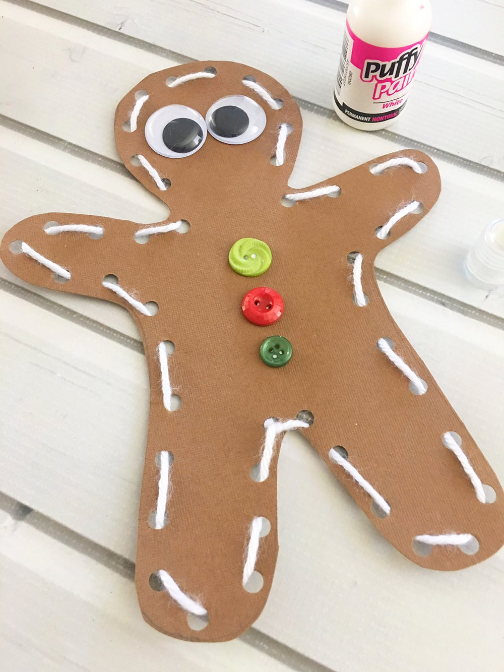 DIY Gingerbread Man Ornaments are an easy and fun holiday activity that will keep the little ones busy for hours! Use as tree ornamnets, gift tags or holiday dinner placecards-Glue two googly eyes onto the face of the gingerbread man and three buttons onto the chest.