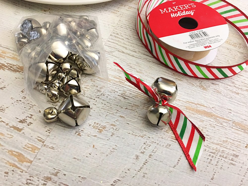 DIY Snowman Decorative Plate is an adorable addition to any Christmas decor! So easy and fun to make with simple supplies from the Dollar Store-attach two bells with a ribbon and tie into a knot
