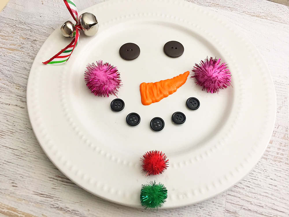 DIY Snowman Decorative Plate is an adorable addition to any Christmas decor! So easy and fun to make with simple supplies from the Dollar Store-glue red and green pom poms vertically underneath the snowman mouth