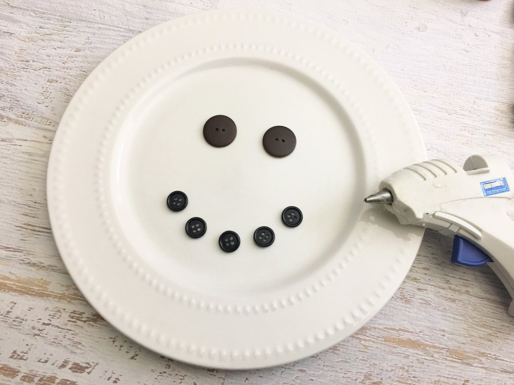DIY Snowman Decorative Plate is an adorable addition to any Christmas decor! So easy and fun to make with simple supplies from the Dollar Store-glue two large buttons on plate for the eyes and five small buttons in the shape of a smile