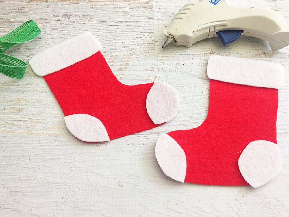 Felt Stocking Christmas Ornaments are an adorable addition to any holiday decor. So easy and fun to make with simple crafts supplies-cut out shapes of heel and toe part of stocking on white felt and glue on red felt stocking
