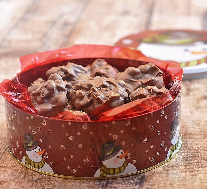 Slow Cooker Chocolate Peanut Clusters in red Christmas snowman tin