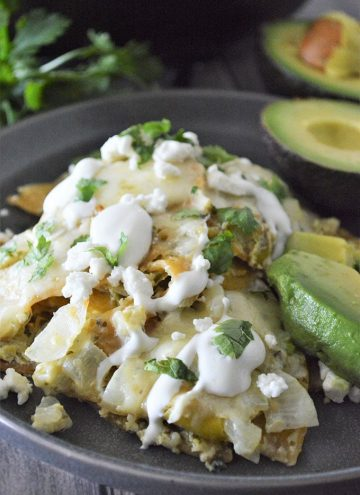 Chilaquiles with Salsa Verde topped with sour cream and chopped cilantro with avocado slices on the side on a plate