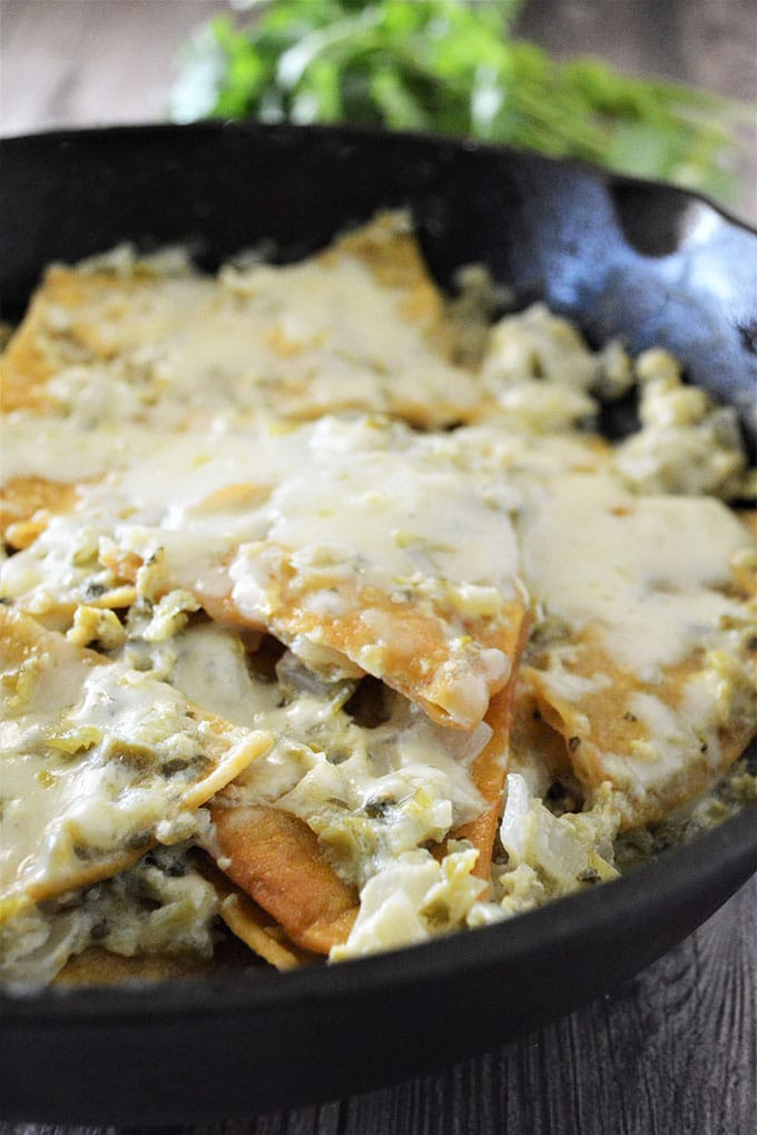 chilaquiles with salsa verde and cheese cooked in a cast iron skillet