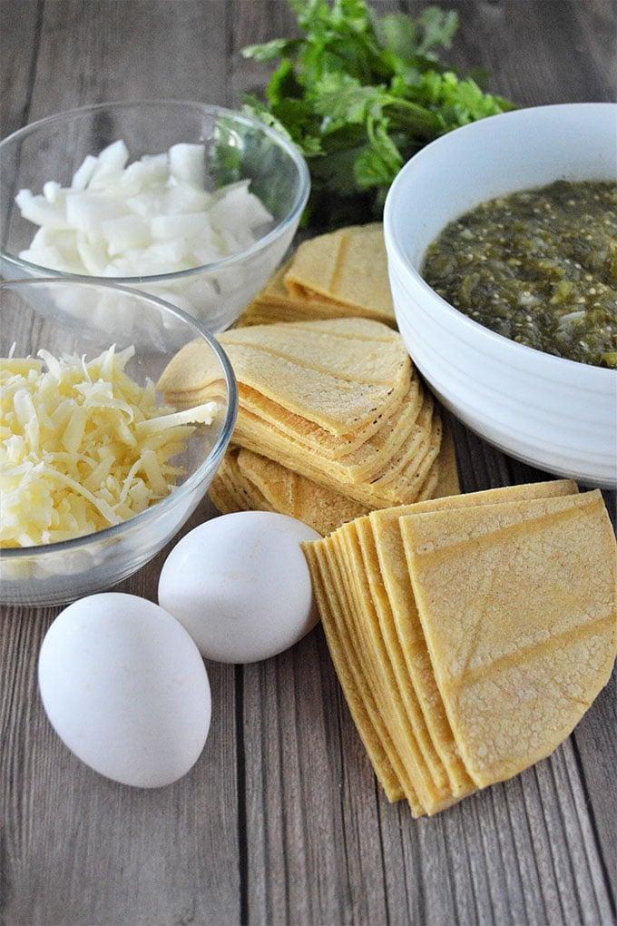 cut corn tortillas, eggs, shredded cheese, tomatillo sauce, chopped onions, cilantro