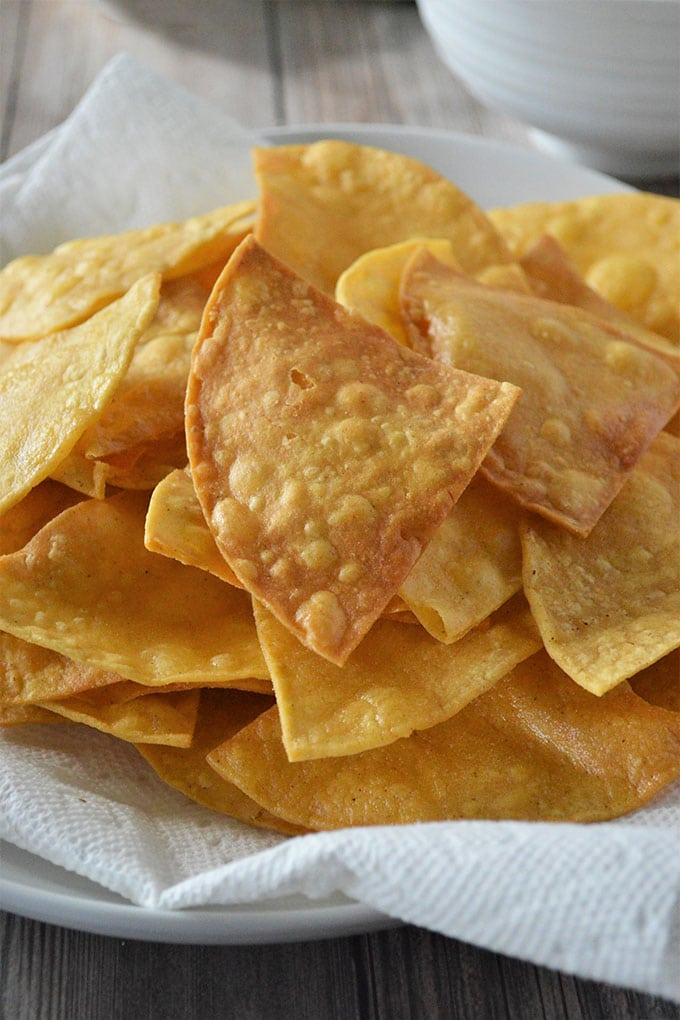 crispy fried tortilla chips on a paper-lined plate