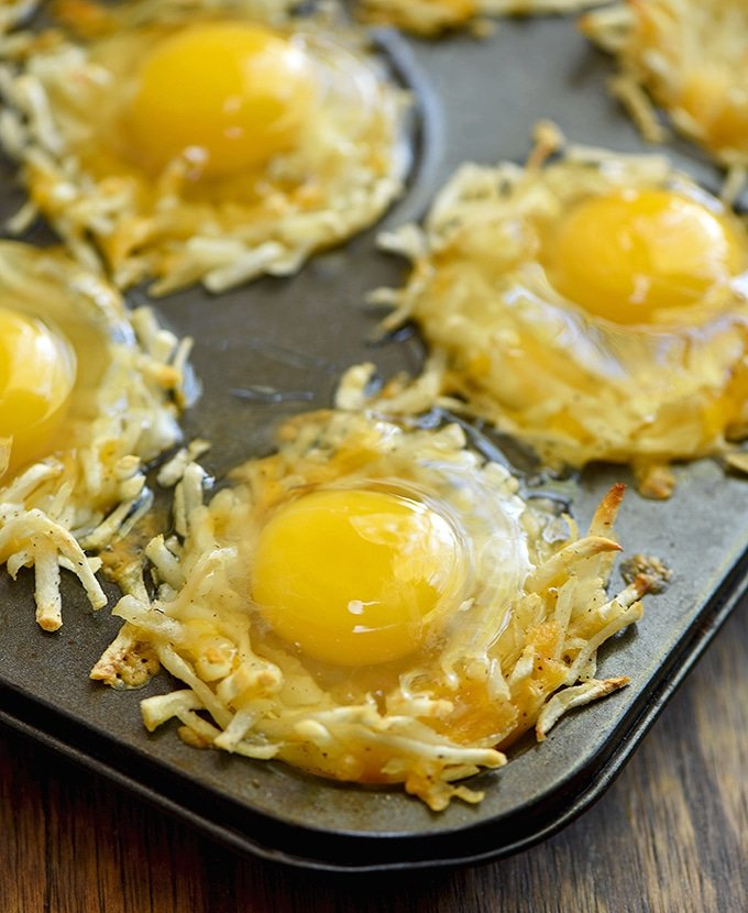 baked hashbrown nest topped with raw egg in a muffin tin ready to bake