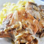 Smothered Pork Chops with Mushroom Gravy with mashed potatoes on a white plate