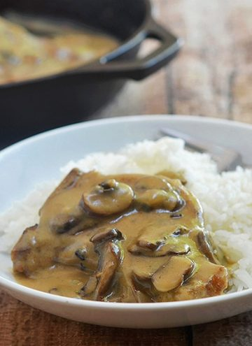 Smothered Pork Chops with mushroom gravy made of from-scratch ingredients and no canned soup. Super-tender pork and flavorful brown gravy perfect with rice, mashed potatoes or noodles. Cooks in one pan with oven and slow cooker options!