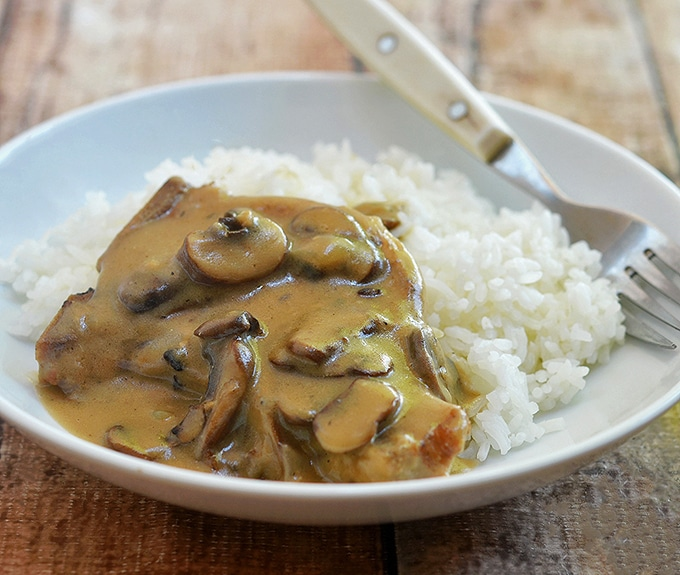 Smothered Pork Chops with Mushroom Gravy served with steamed rice.