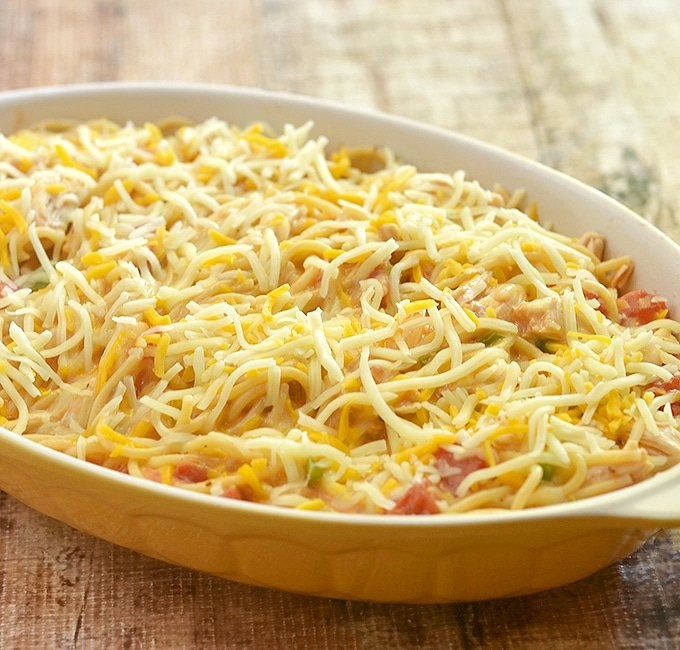 Chicken Spaghetti topped with shredded cheese and ready to bake in the oven
