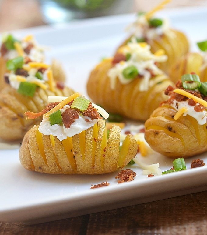 Mini Hasselback Potato Bites loaded with sour cream, crisp bacon, shredded cheese and green onions.
