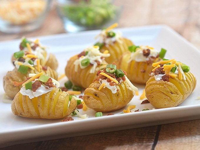 Mini Hasselback potatoes topped with sour cream, bacon, and green onions