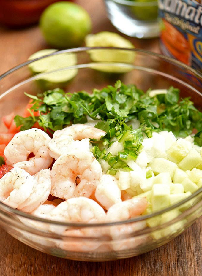 cooked shrimp, tomatoes, cucumber, onions, cilantro, and chili peppers in a clear bowl for Mexican-style shrimp cocktail