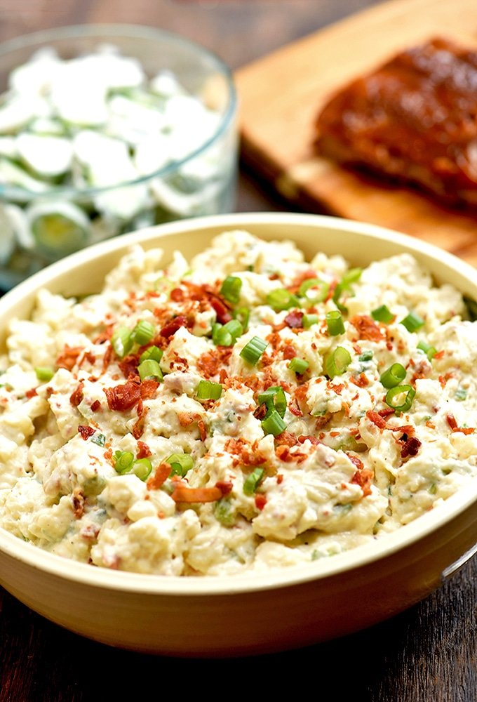 This loaded potato salad is topped with bacon, and green onions for tons of delicious flavor!