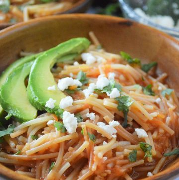 Sopa Seca de Fideo with avocadoes and crumbled cheese in a wooden bowl
