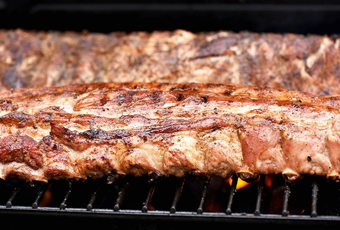 two racks of baby back ribs on the grill
