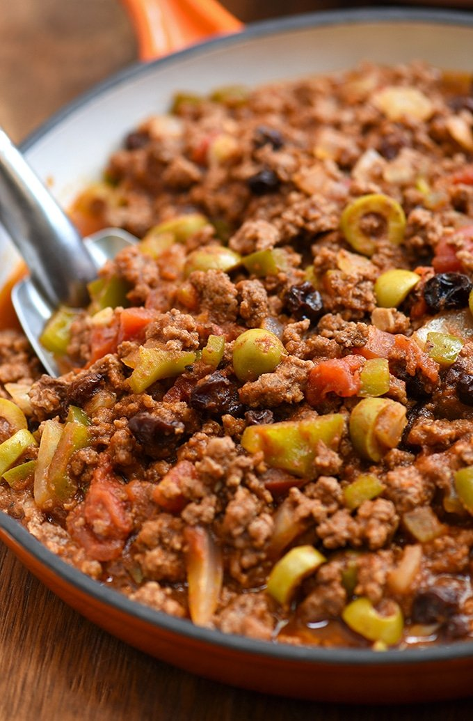 Cuban-style picadillo recipe with green olives, raisins, bell peppers, and tomato sauce in a skillet