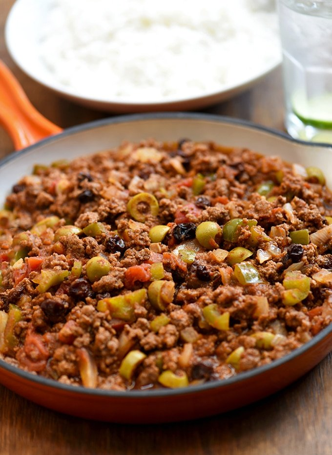 Cuban picadillo served in a orange skillet with a side of rice