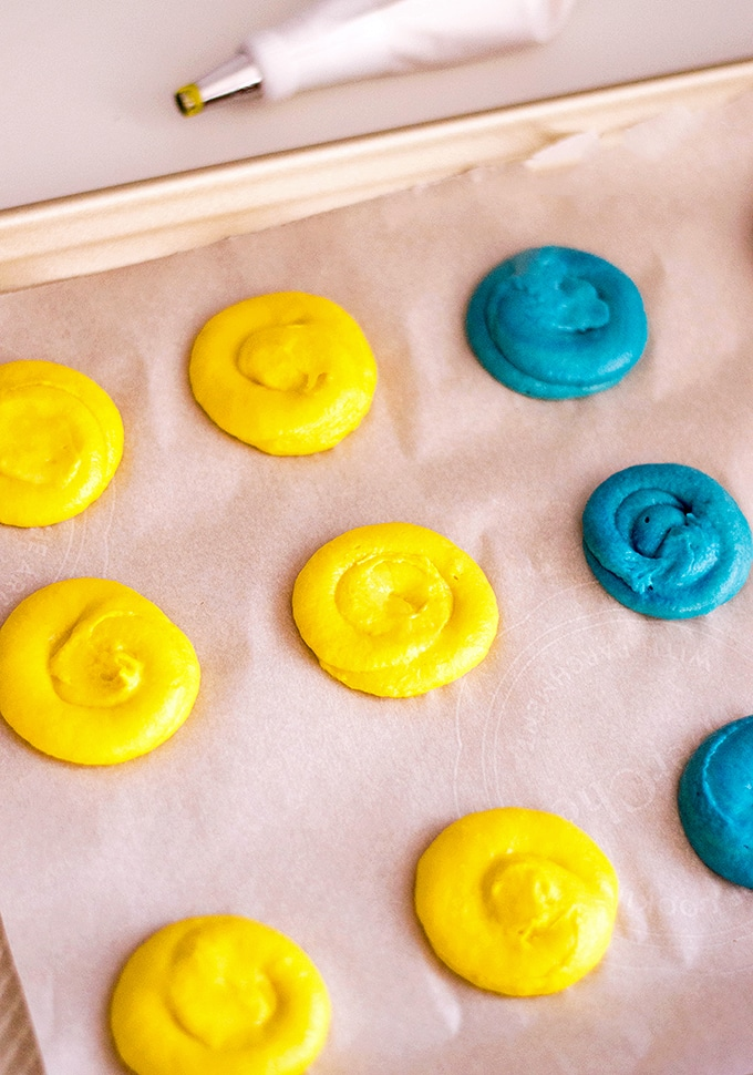 Piping the colored Minion whoopie batter on a baking sheet