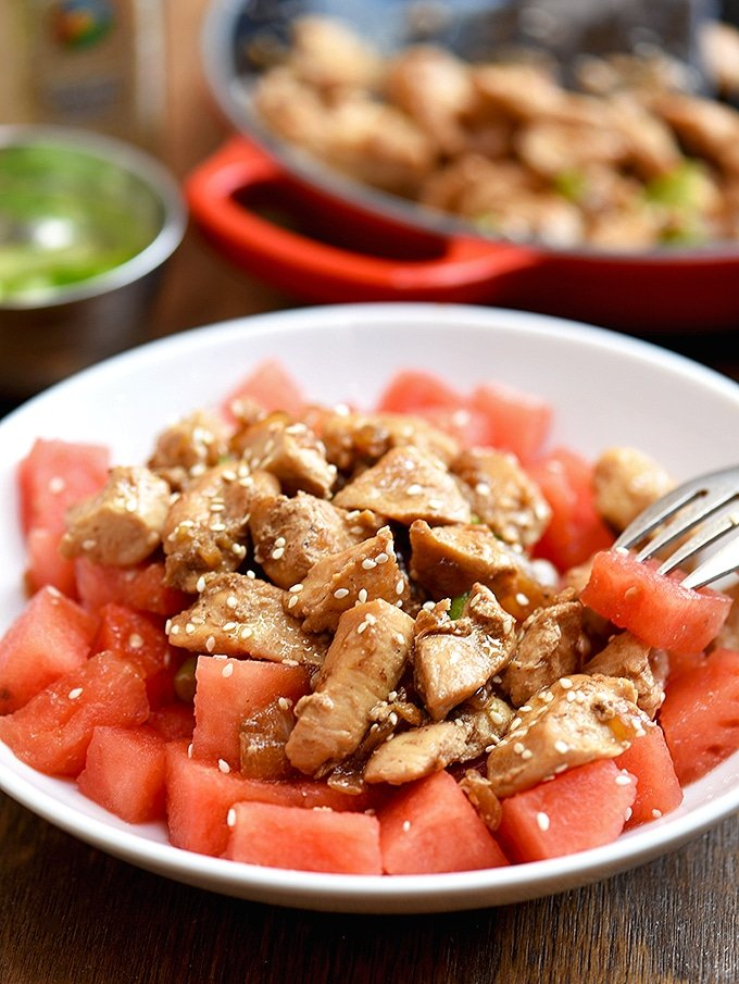 sesame chicken and watermelon served on a plate