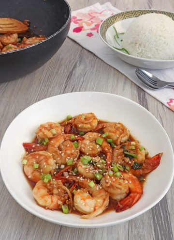Shrimp in Soy Sauce in a white bowl with a black pan and a plate of steamed rice on the side
