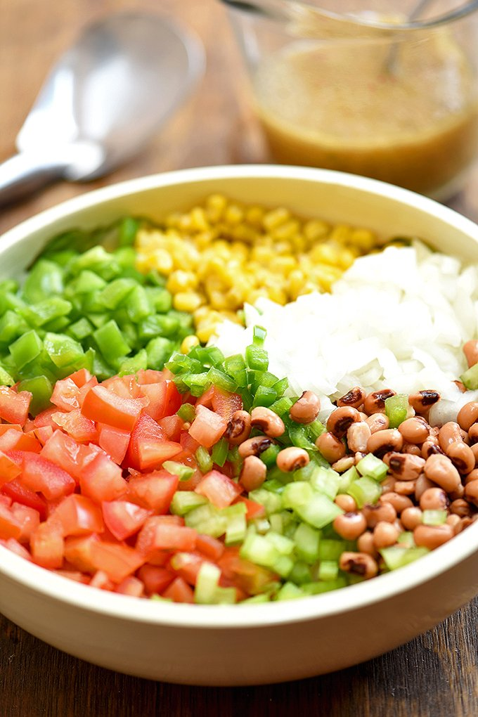 black-eyed peas, grilled corn kernels, and tomatoes, bell peppers, onions, and jalapenos in a large bowl for making texas caviar