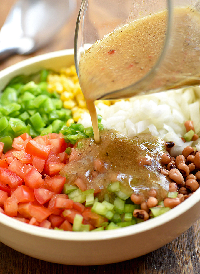 adding Italian dressing to a bowl of Texas caviar