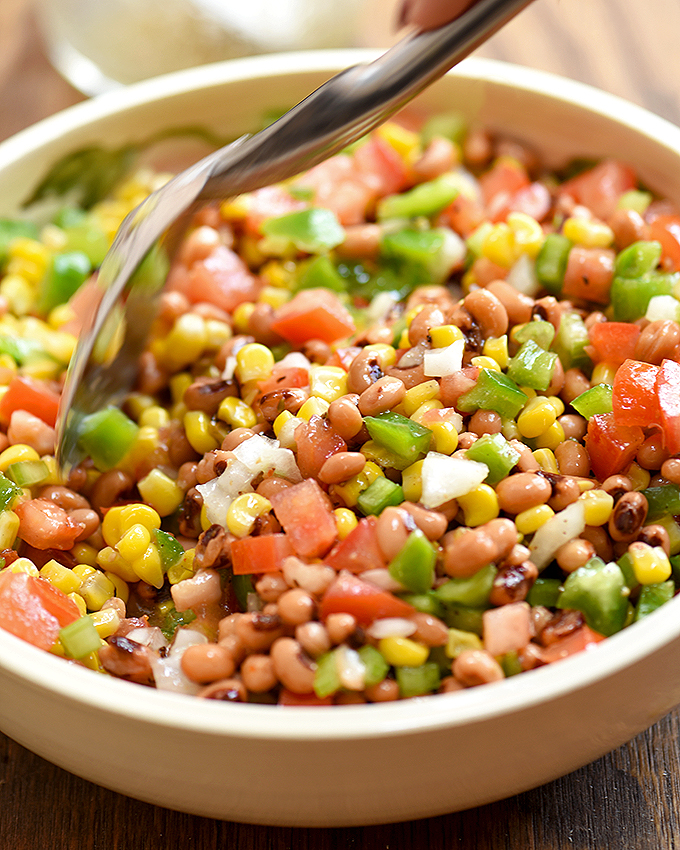 mixing the ingredients for Texas caviar together with a spoon in a large bowl