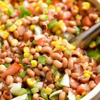Texas Caviar dip with black-eyed peas, grilled corn, tomatoes, bell peppers, onions, jalapeno, and Italian dressing in a serving bowl