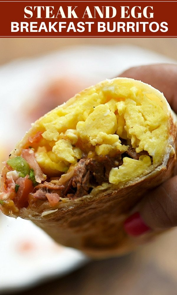 hand holding a breakfast burrito half filled with steak, eggs, and tomato salsa