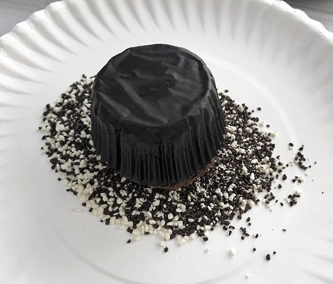 frosted chocolate cupcake being dipped in candy sprinkles