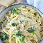 pasta alfredo with broccoli and parmesan cheese in a skillet