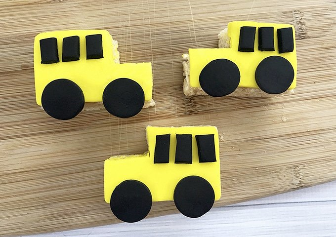 yellow Rice Krispies treats shaped like a school bus with black fondant wheels and windows