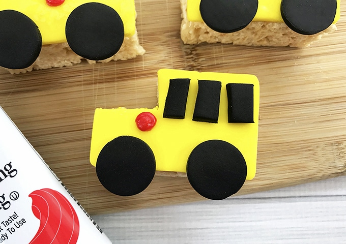 yellow Rice Krispies treats shaped like a school bus with black fondant wheels, windows and red light