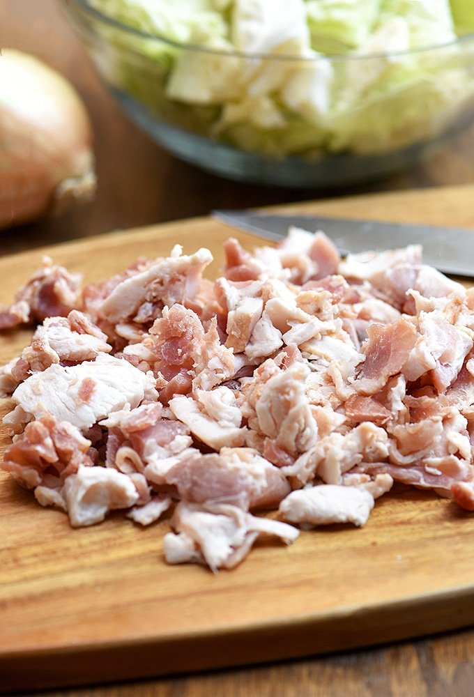 chopped bacon ends and pieces on a cutting board, a bowl of chopped cabbage, and a whole onion