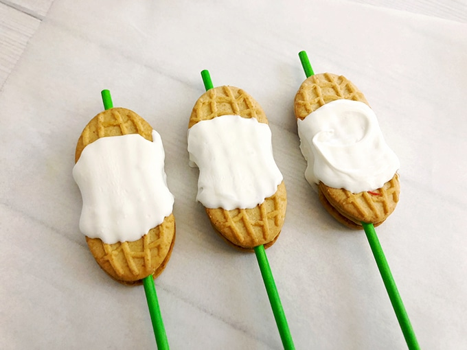 nutter butter cookies on green lollipop sticks coated in the middle with white candy