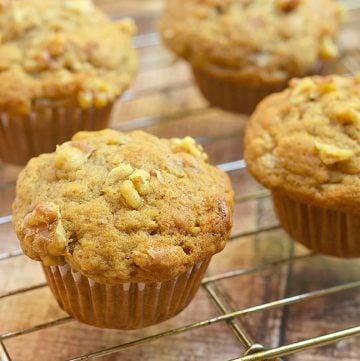 Banana Nut Muffins with walnuts on a wire rack