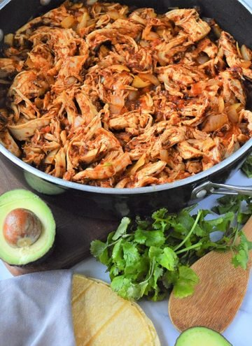 Mexican Chicken Tinga in a red skillet with corn tortillas, cilantro, and avocado on the side